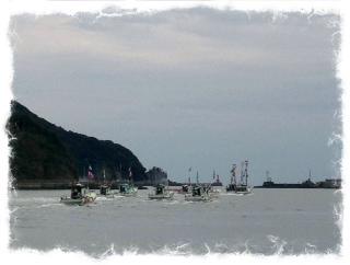 去っていく大漁旗の船団